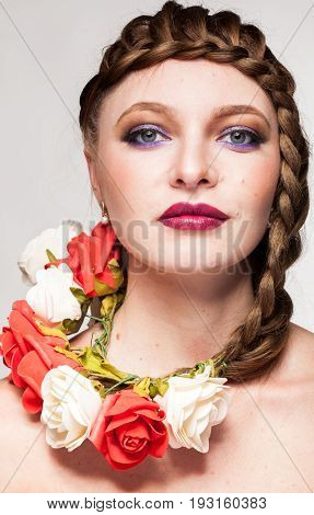 Woman with flowers arround her neck in studio photo. Beauty and fashion. Glamour and summer
