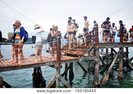 KOTA KINABALU MALAYSIA- 24 JUN 2017: Tourists walk on Manukan Island footbridge in Malaysia. The Manukan Island Resort is a hideaway that is one of the five tropical islands that comprise the Tunku Abdul Rahman Park.