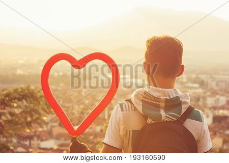 Boy with hoodie holding a heart ballon in front of city in the evening sunshine