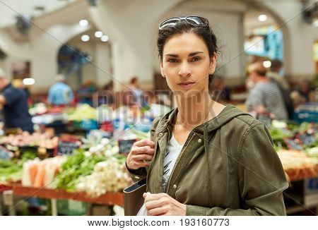 Young woman at greengrocer's shopping for fruits and vegetables.