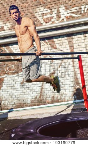 Half-naked muscular man going outdoor fitness training on parallel bars