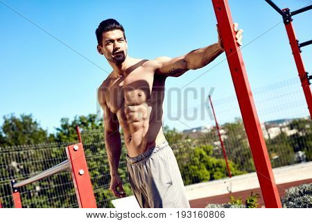 Portrait of half-naked muscular handsome man at outdoor gym.