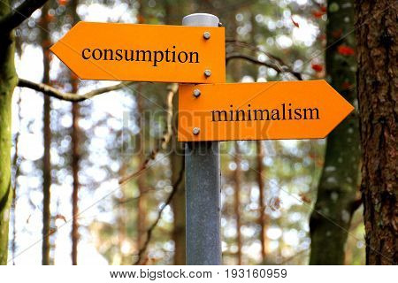 Minimalism and consumption written on a hiking sign in the forest