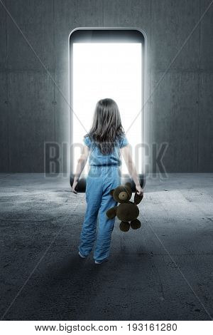 back of girl with teddy bear in the hand standing in front of gigantic lighten smartphone