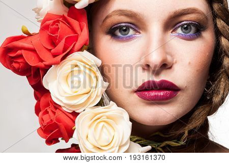 Woman with flowers arround her head in studio photo. Beauty and fashion. Glamour and summer