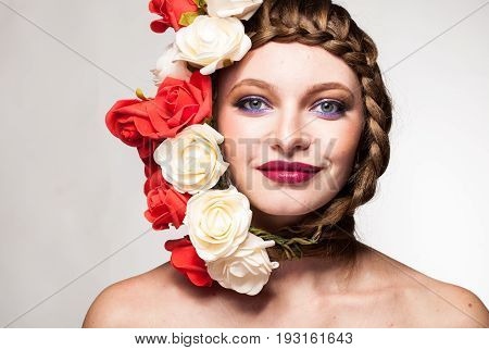 Smiling Woman with flowers arround her head in studio photo. Beauty and fashion. Glamour and summer