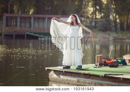Bride on a wakeboard on the lake. She was about to swim in her dress.