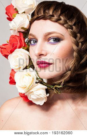 Woman with flowers arround her head and makeup in studio photo. Beauty and fashion. Glamour and summer