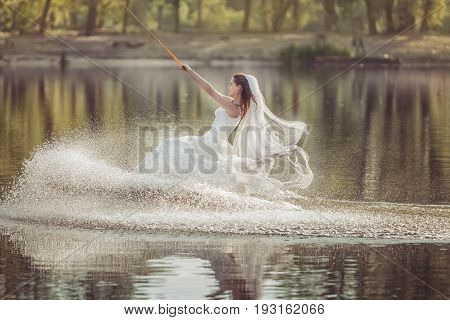 Bride in a wedding dress on a wakeboard slides on the lake.