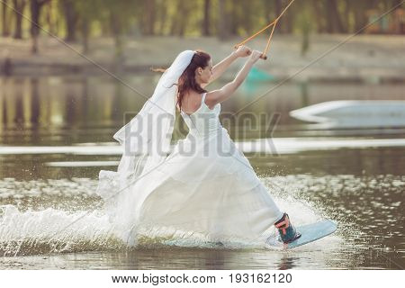 Bride in a wedding dress and veil on her head is engaged in extreme sports she is on a wakeboard.
