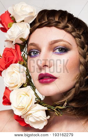 Young Woman with flowers arround her head in studio photo. Beauty and fashion. Glamour and summer