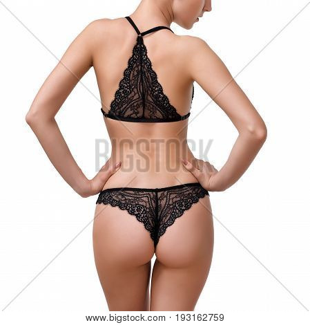 Slim, beautiful woman in lace lingerie isolated on white background. Body parts, close up of woman half body length wearing black stylish underwear. Ideal waist, perfect figure, erotic, fashionable clothes