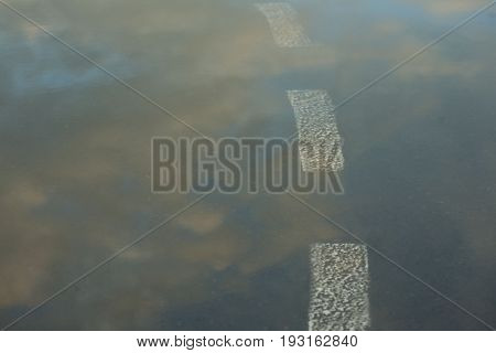 Reflection of the sky in the wet asphalt and puddle after the rain in the setting sun. Road marking going into the water. Close up view from the level of the dividing line. Road to the clouds