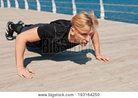 Confident man doing push-ups on esplanade at the sea. Horizontal outdoors shot.