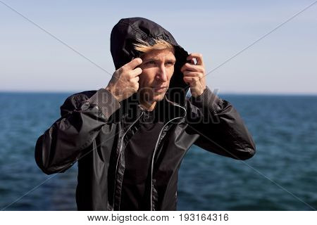 Young man wearing black windbreaker and looking away on background of sea.