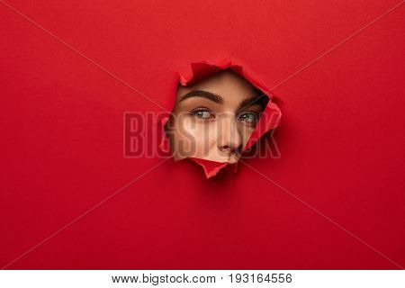Young female face looking out of hole torn in red paper.