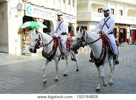 DOHA, QATAR - APRIL 9, 2017: Mounted police patrol the Souq Waqif market in central Doha  mainly as a cultural spectacle for tourists