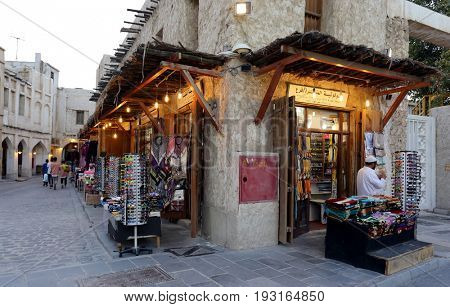 DOHA, QATAR - APRIL 9, 2017: Backstreets of Souq Waqif, in Doha, with shops lit at sunset.