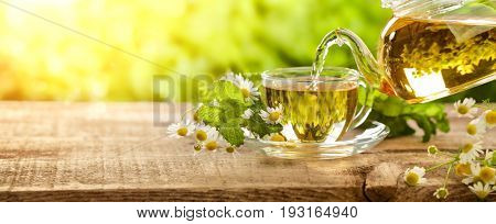 Pouring tea from teapot into cup,natural background