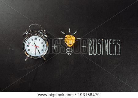 Business Concept Made Of Light Bulb Symbol And Alarm Clock On Blackboard