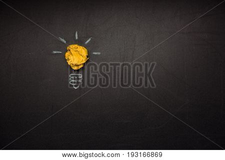 light bulb symbol made of crumpled paper on blackboard
