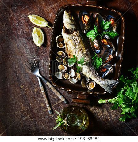 Top view of variety mussels and oven baked seabass with lemon olive oil on old wooden table with copy space.