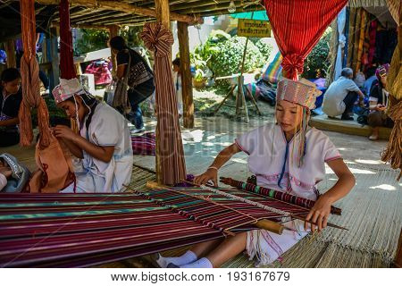 CHIANGMAI THAILAND - JANUARY 24 2015: Hill tribe girl is demonstrating weaving in 22nd Traditional Skirt Fabric and The Indigenous Product and Culture Festival in Mae Chaem of Chainagmai Thailand