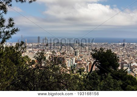 Barcelona skyline with sea and Sagrada Familia clouds and trees from park Güell