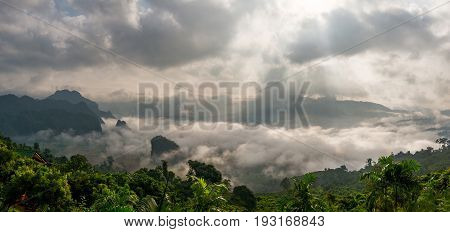 Landscape misty panorama. Fantastic dreamy sunrise on the mountains with a beautiful view. Foggy clouds above the landscape.