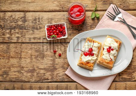 Tasty puff pastry dessert with berries and whipped cream on plate