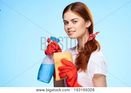 Young beautiful woman on a blue background, housework, cleaning.