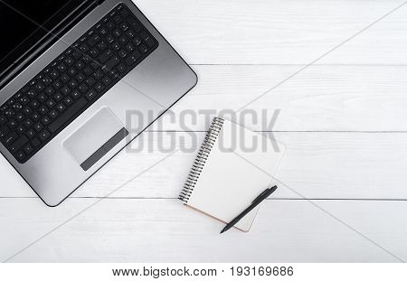 Wooden white office desk table with open blank laptop computer and empty white diary with pen free space. Top view with copy space. Grey laptop on wooden background