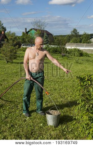 A man pours water from a hose into a bucket at his dacha