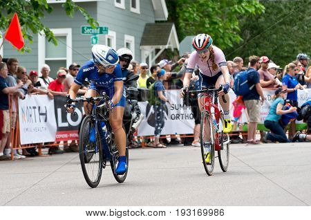 STILLWATER, MINNESOTA/USA - JUNE 18, 2017: Two pro cyclists chase leaders at the 2017 North Star Grand Prix Women's Stillwater Criterium. It is the final stage of a six-stage annual race event.  STILLWATER, MINNESOTA/USA