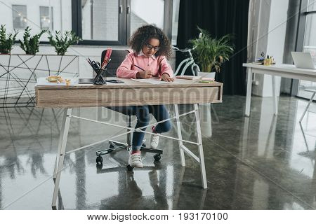 Little African American Girl Pretending To Be Businesswoman And Working In Modern Office