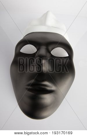 Black And White Masks Joined On White Reflective Background. Wide Angle, Vertical Image, Top View