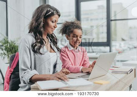 Little Daughter Helping Mother Working On Laptop At Business Office, Work And Life Balance Concept