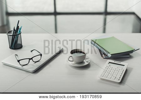 laptop eyeglasses and cup of coffee with office supplies on tabletop