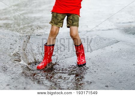 Child wearing red rain boots jumping into a puddle. Close up. Kid having fun with splashing with water.