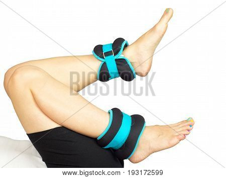 Detail of a woman's feet exercising with ankle weights, isolated