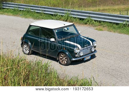 IVREA, ITALY - AUGUST 20, 2015: A classic green Mini Cooper vintage parked on a street