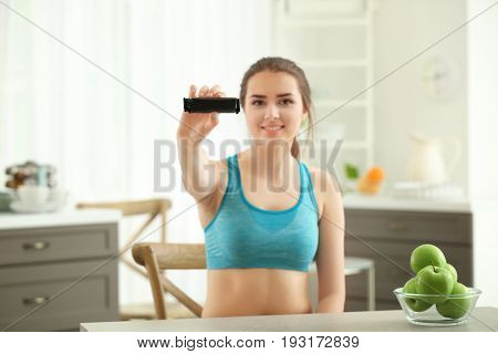 Beautiful young woman with energy bar sitting at table in kitchen. Diet concept