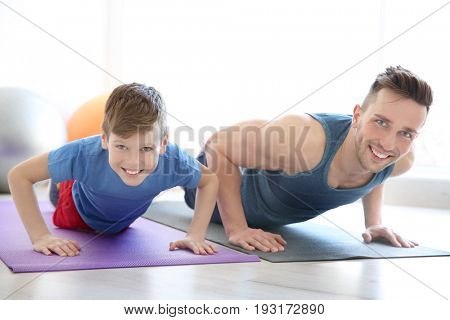 Dad and son doing push-ups in gym