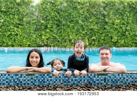 Photo of happy family in swimming pool smiling at camera in summer holiday resort. Happy family summer vacation with father mother daughter and brother.