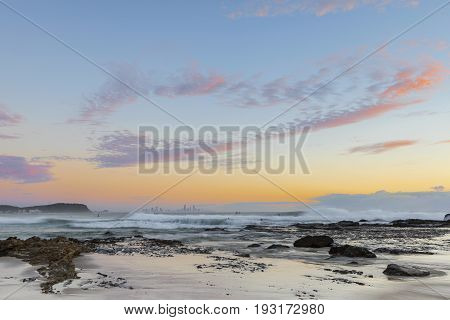 Colorful sunrise clouds and ocean waves with the beach below at Currumbin Rock, Gold Coast