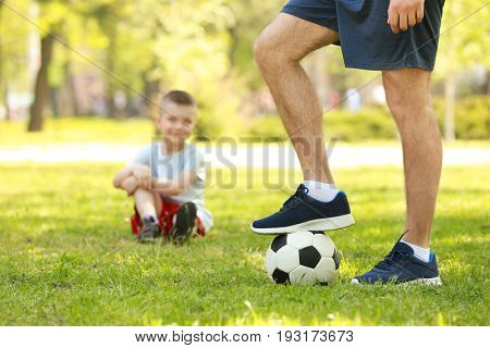 Young man with soccer ball in green park and his blurred son on background