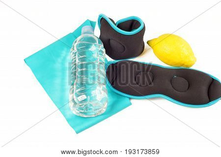 Sports equipment ankle weights and band with lemon and bottle of water, isolated on white background
