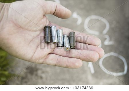 Male hand with empty gun cartridges the chalk outlines in the blurred background