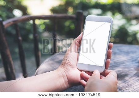 Mockup image of hands holding white mobile phone with blank screen on vintage wooden table and nature background