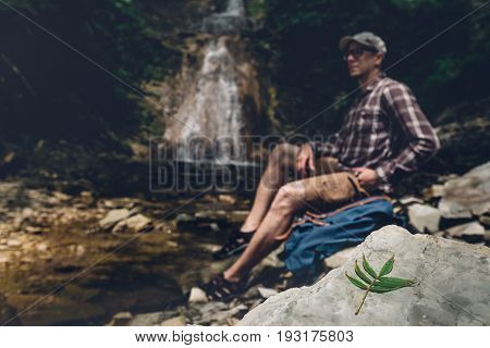 Hiker With Backpack Sits On The River And Enjoys Surrounding View Selective Focus. Exploring Adventure Hiking Concept